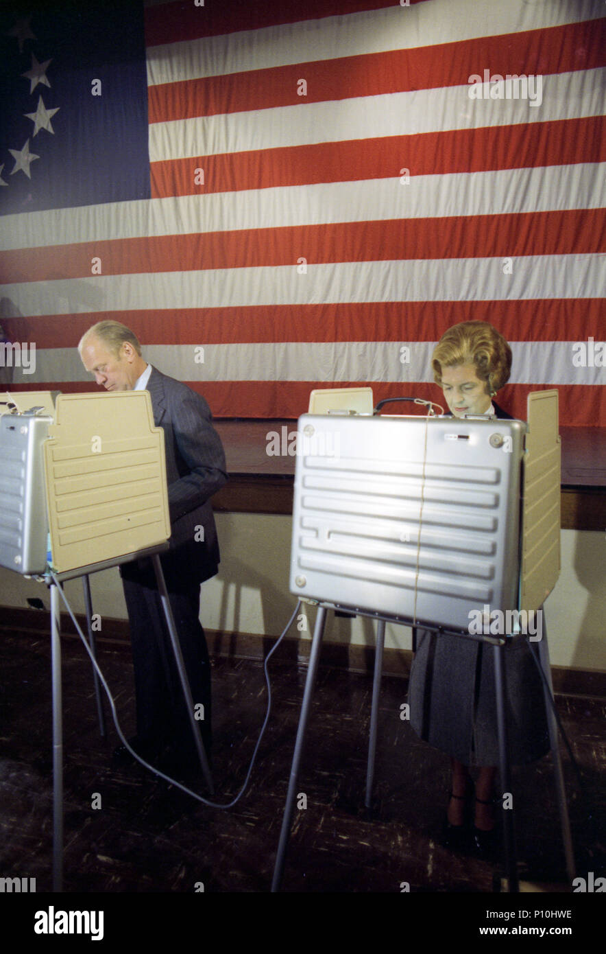 1976, November 2 - Wealthy Elementary School - Auditorium - East Grand Rapids, MI - Gerald R. Ford, Betty Ford - standing in voting booths; voting; partially obscured by walls of voting machine; medium range - Campaign Trip to Michigan - Voting in Presidential Election - Stock Image