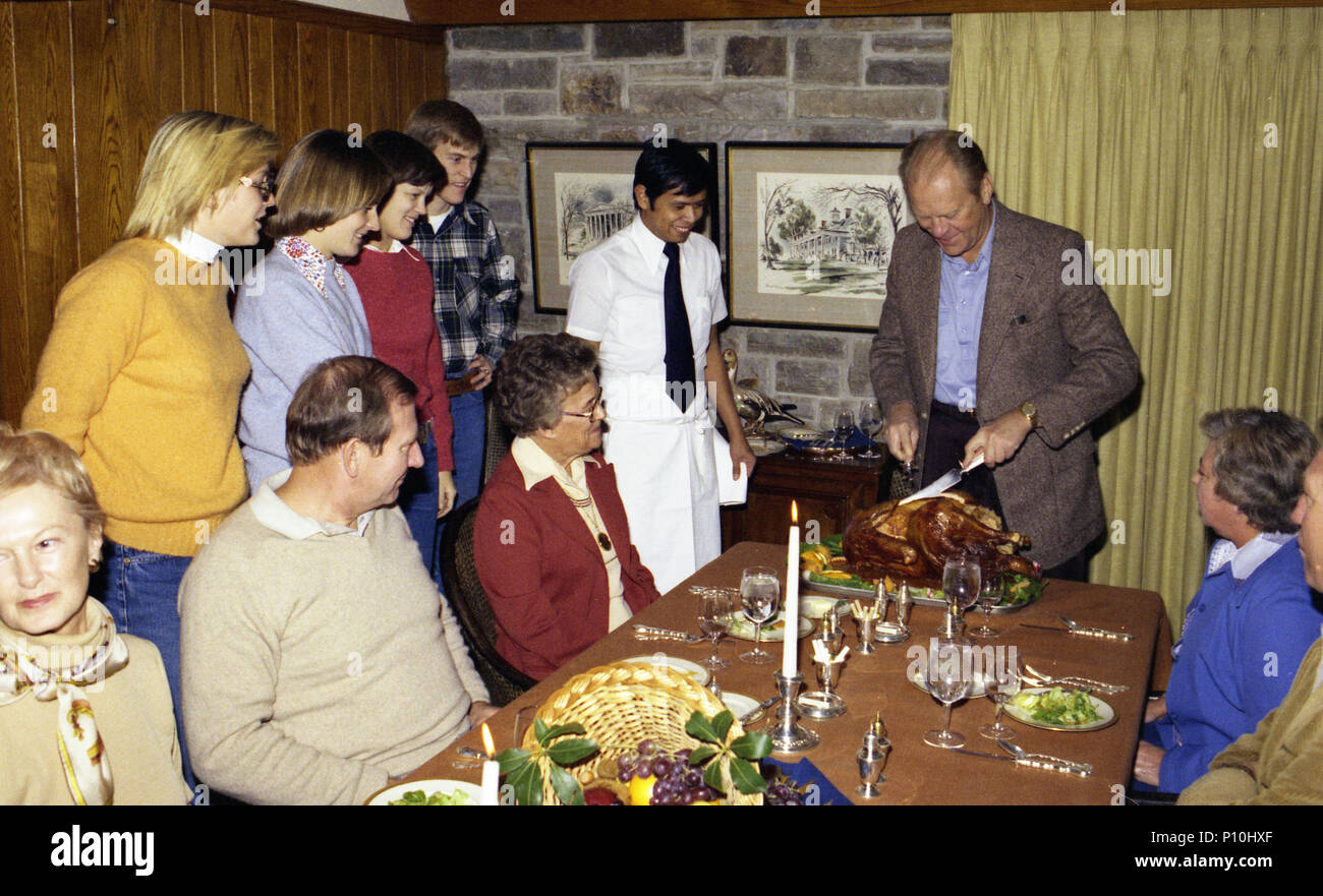 1976, November 25 – Camp David - Aspen Lodge - Living Room – Gerald R. Ford, Betty Ford, Steve Ford, Mike & Gayle Ford, Susan Ford, Tom & Janet Ford; Jim & Barbara Ford; Nieces, Nephews, Cousins; Aspen Lodge Stewards & Cook – seated, standing around table; GRF carving turkey in several frames; GRF complimenting cook; others applauding in some frames; various angles and distances; all not in every frame – Thanksgiving Trip to Camp David, Maryland - Prior to Ford Family Thanksgiving Dinner - Stock Image