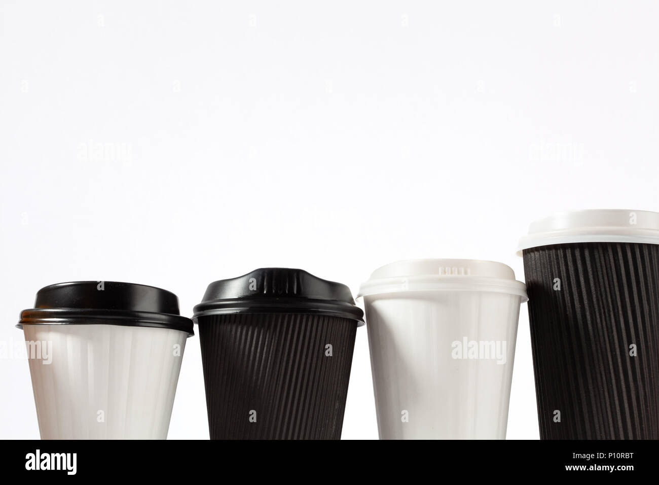 Four plastic coffee cups in a row on white background with copy space Stock Photo