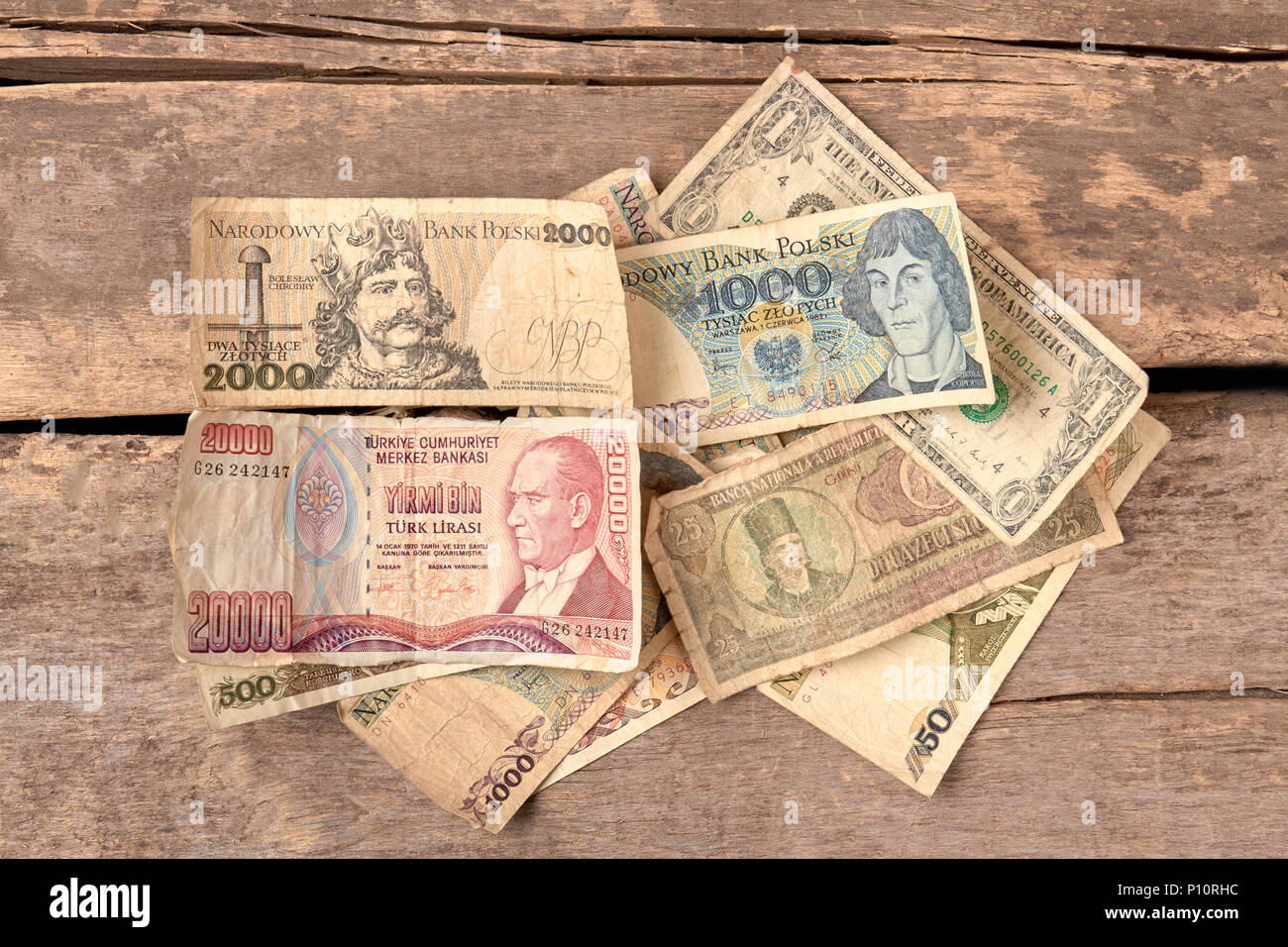 Colorful old world paper money Wooden desk background Stock