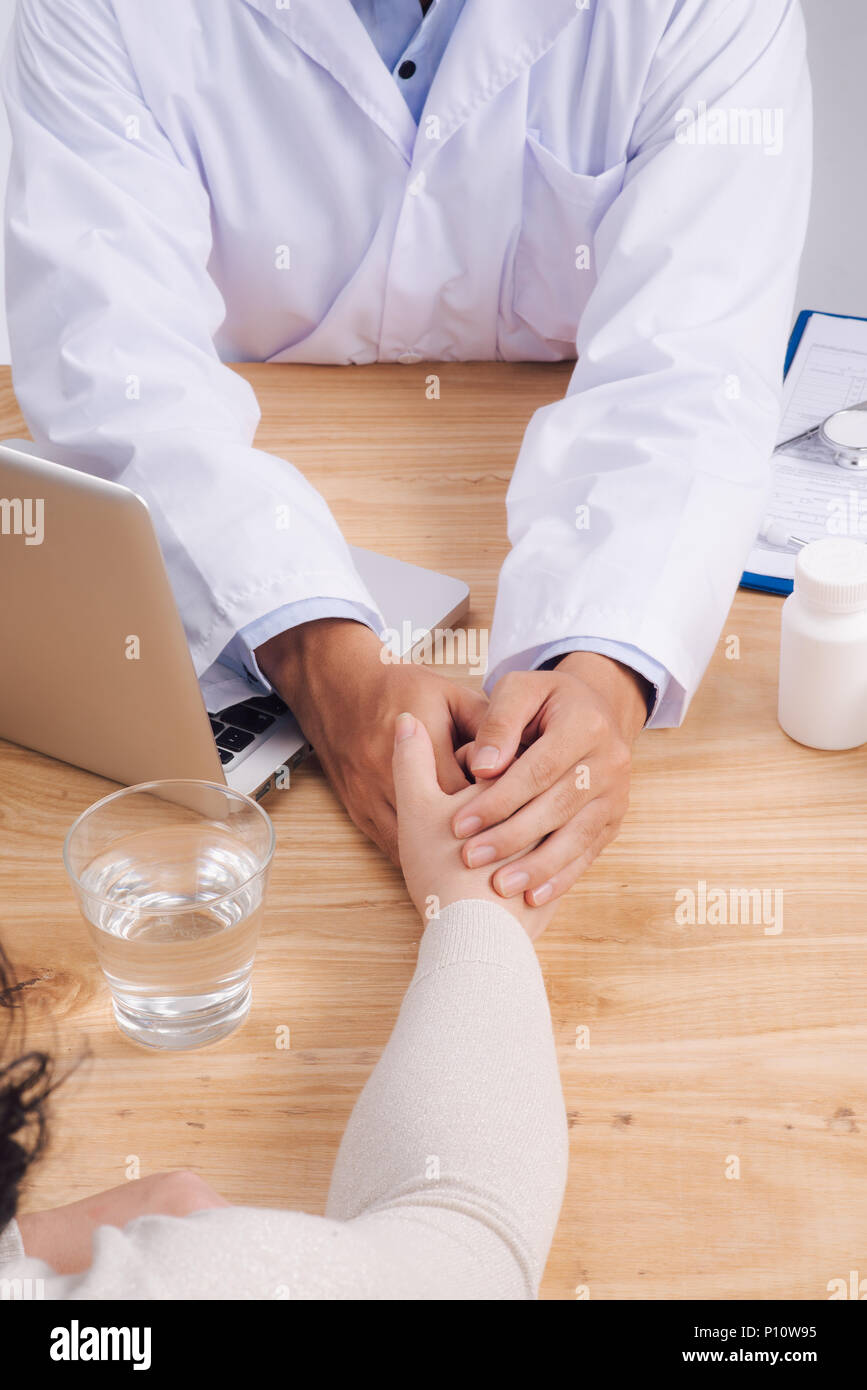 Friendly doctor hands holding patient hand sitting at the desk for encouragement, empathy, cheering and support while medical examination. Bad news le - Stock Image