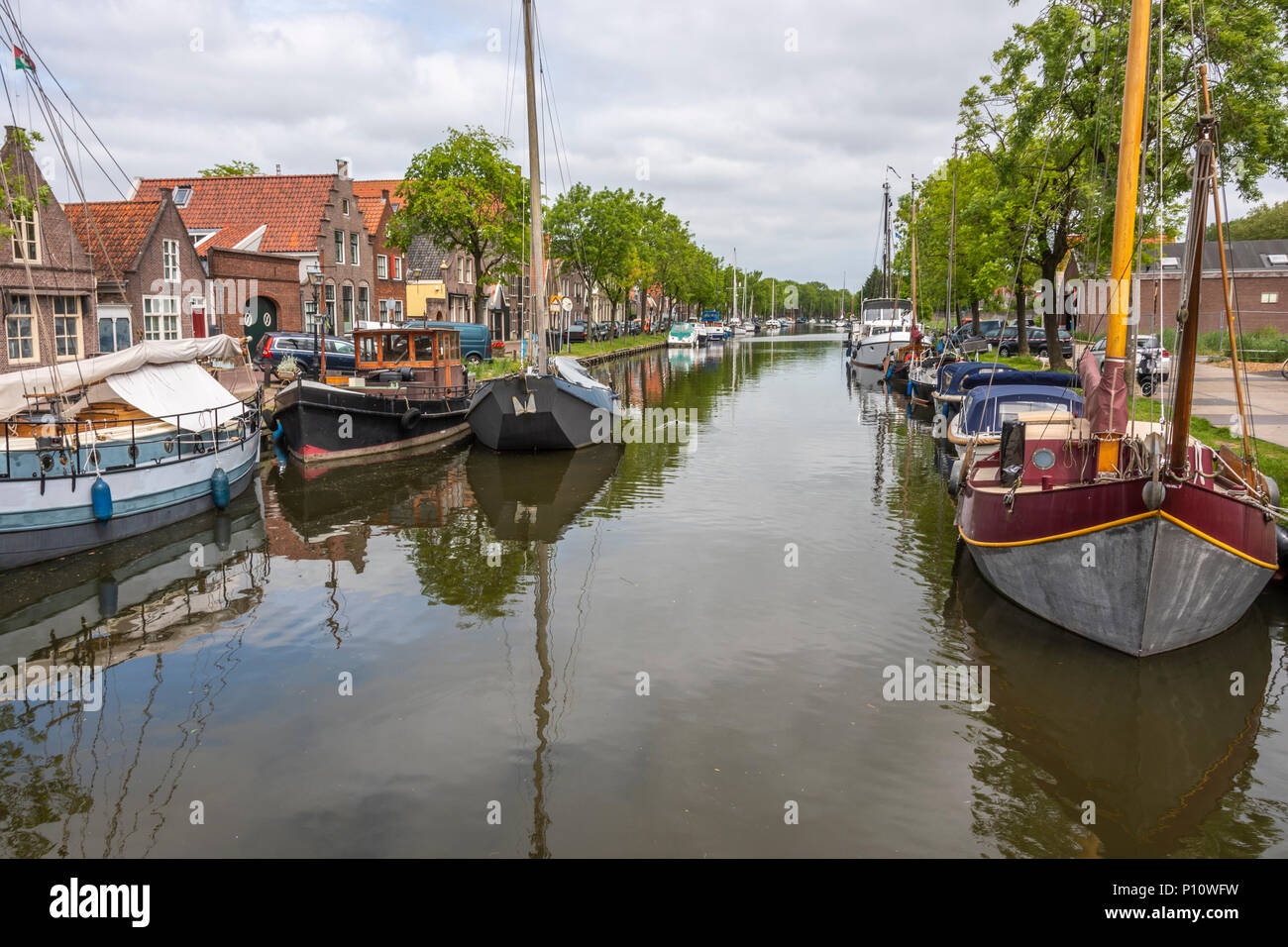 canal and boats with houses on the sides of them in the city of edam. netherlands - Stock Image