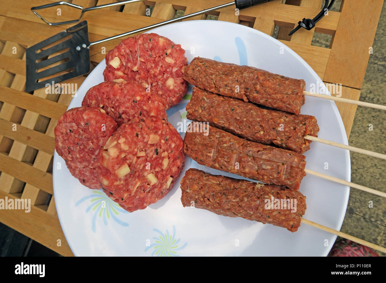 Dangers of food poisoning from summer BBQ meat, Sausages, beef burgers, Kebabs, under-cooked or raw - Stock Image