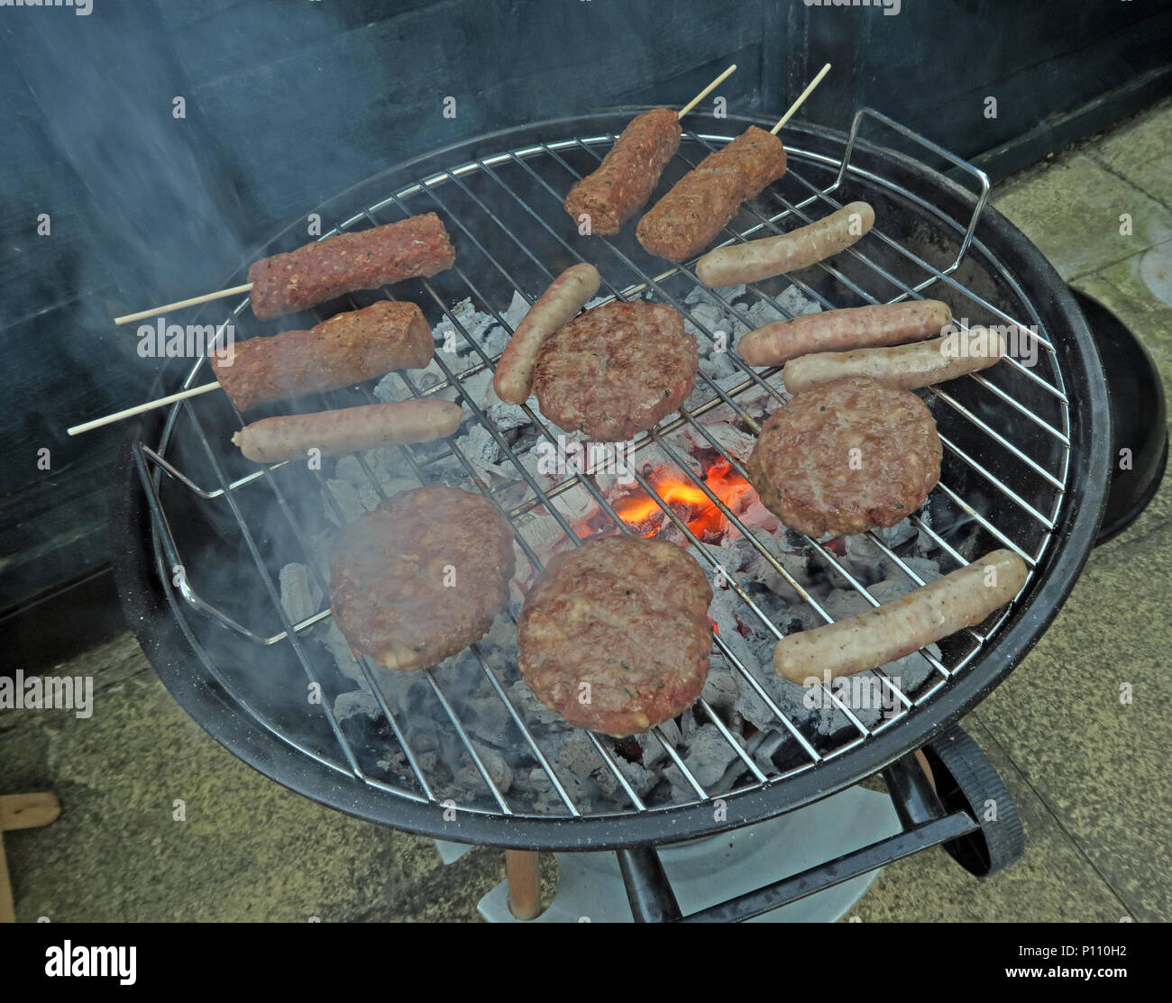 Well cooked BBQ meat on summer garden barbecue - Stock Image