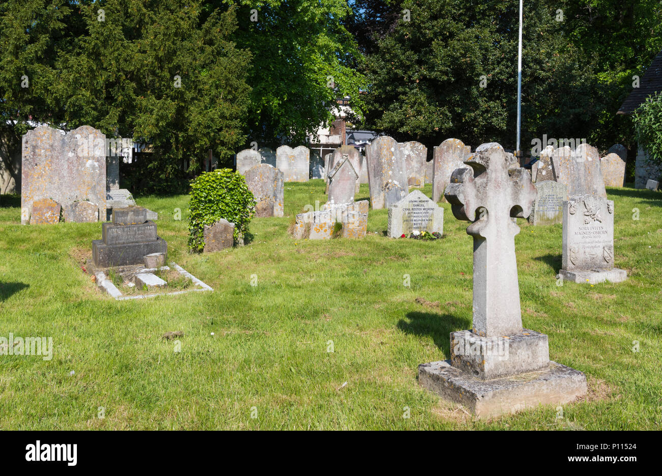 Small cemetery or graveyard with old gravestones on well kempt cut grass at the St Peter & St Paul Church in Rustington, West Sussex, England, UK. - Stock Image