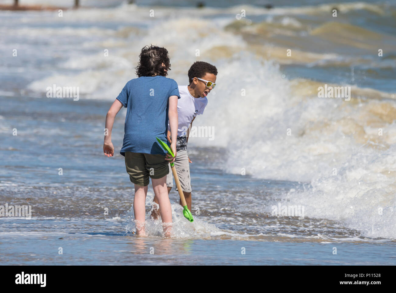 Pair of young boys on a beach at the seaside playing as the waves break nearby in England, UK. Boys look to be of different ethnic backgrounds. - Stock Image