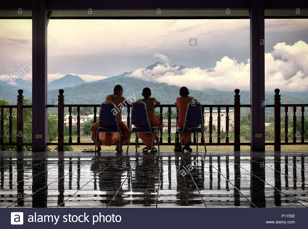 three young buddhist monks looking the mountains in a buddhist monastery in thailand - Stock Image