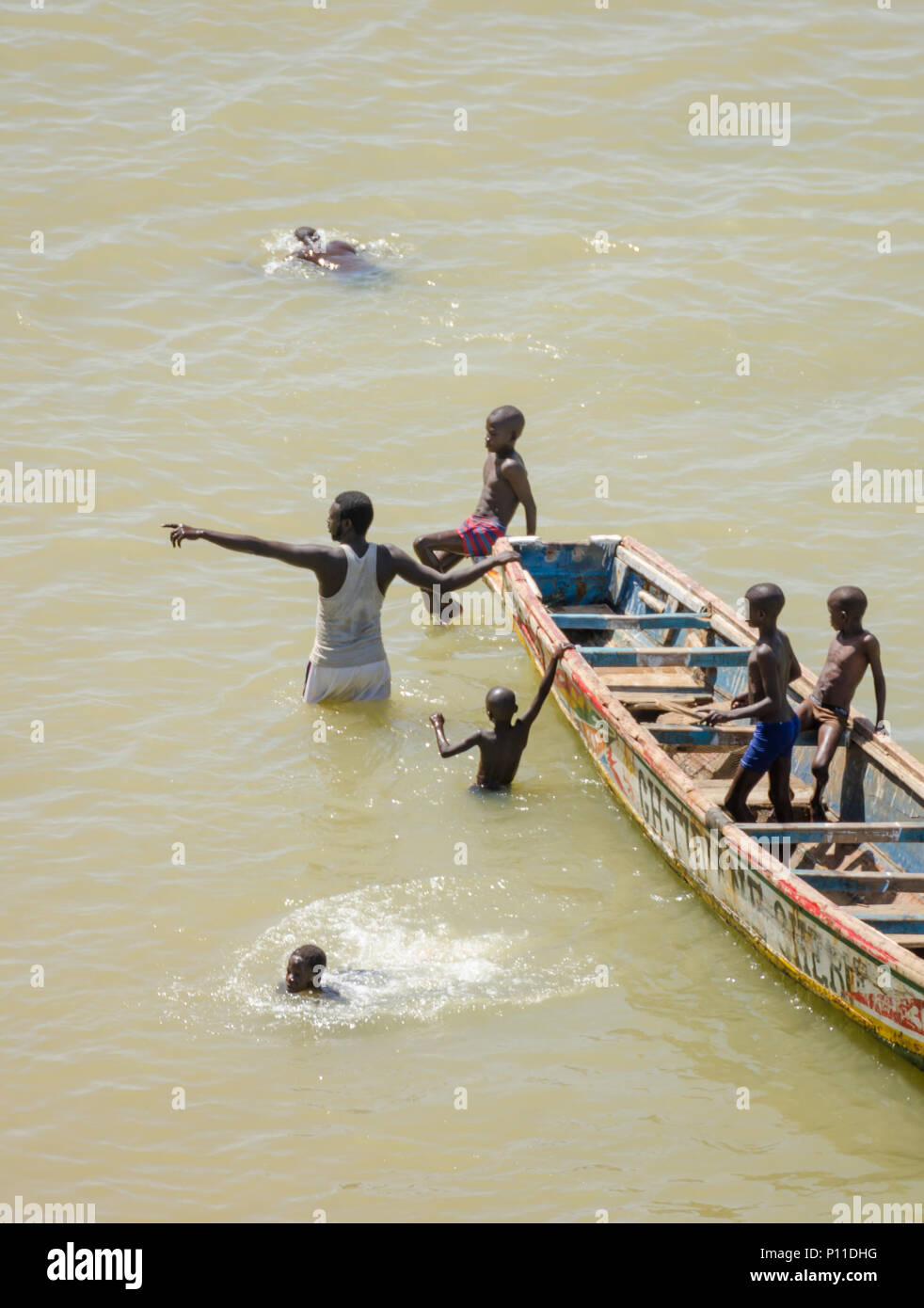 Saint-Louis, Senegal - October 20, 2013: Unidentified African children and grown man swimming next to wooden boat - Stock Image