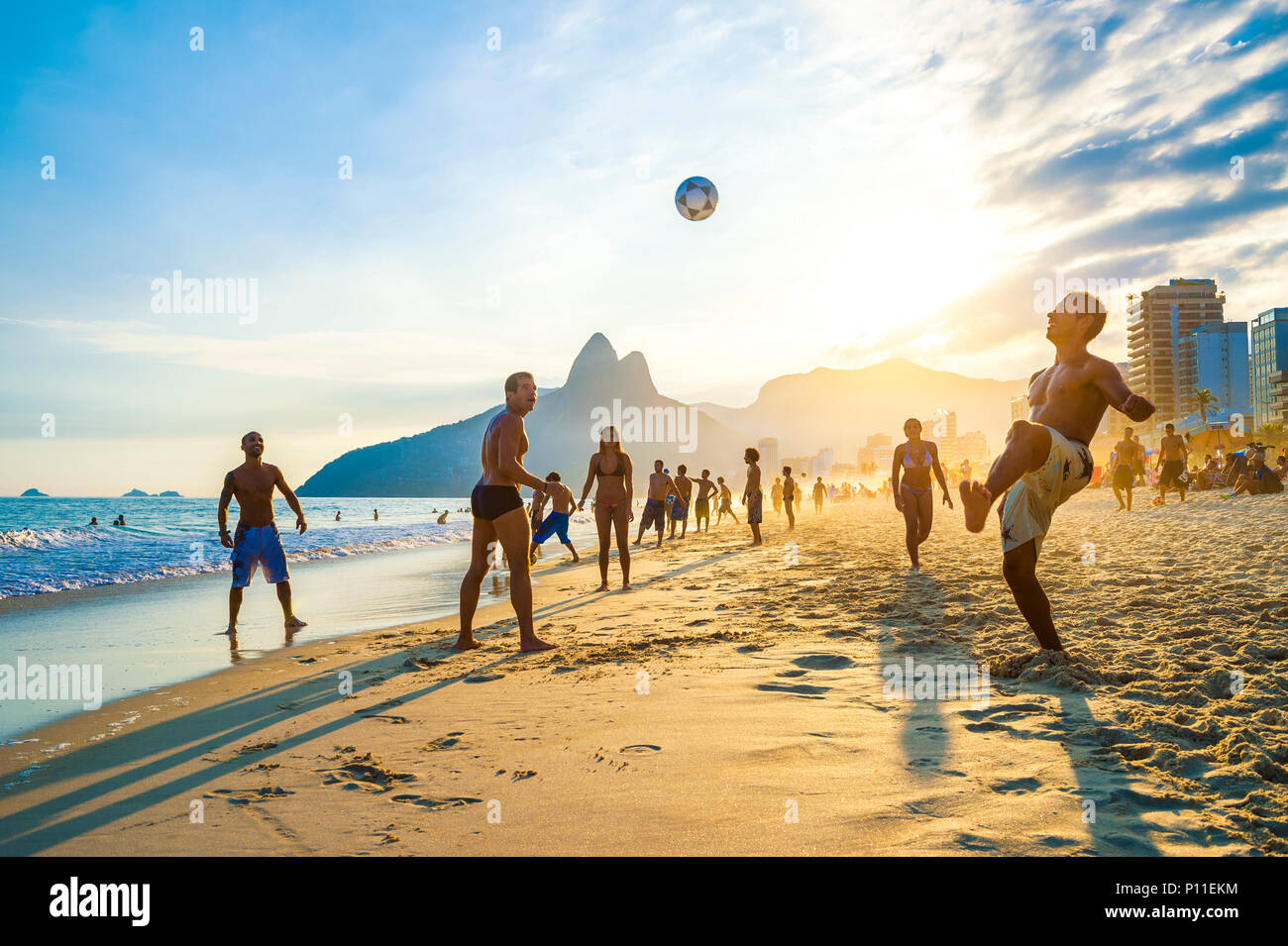 RIO DE JANEIRO - APRIL 01, 2014: Groups of young Brazilians play keepy uppy, or altinho, at sunset on the shore of Ipanema Beach at Posto 9 - Stock Image