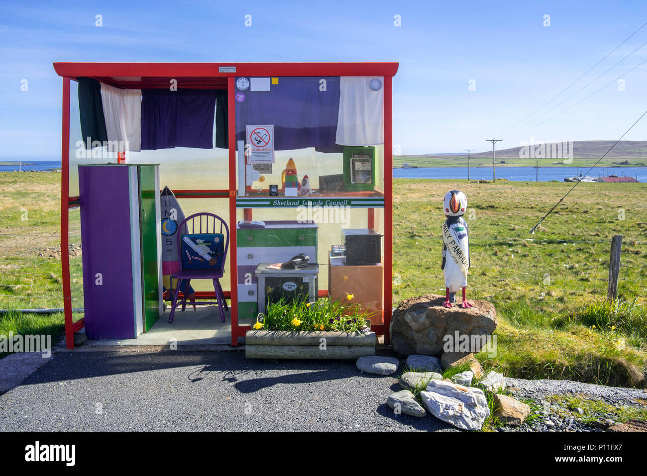 Amusing bus stop shelter furnished and decorated with home comforts near Baltasound, Unst, Shetland Islands, Scotland, UK - Stock Image