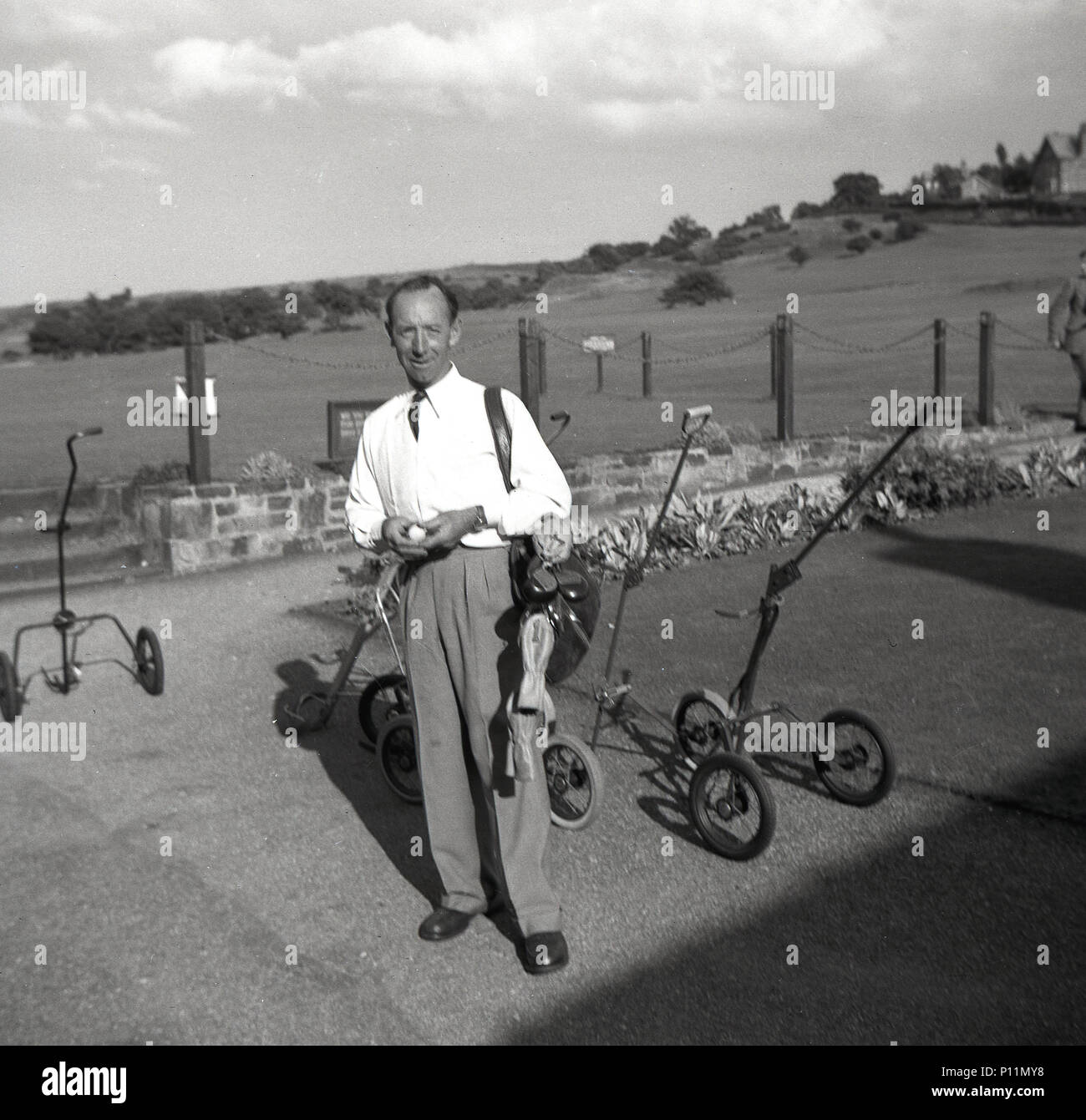 1953, historical, smartly dresssed adult male golfer in shirt and tie, with his clubs on his shoulder about to start his round of golf, England, UK. - Stock Image