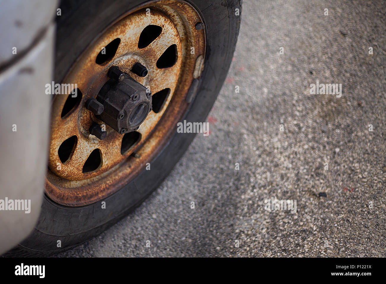 A closeup view of a heavily used car tyre that seems abandoned a longtime ago. There are also rusted rim hubcap and  screws that badly needs maintenan - Stock Image