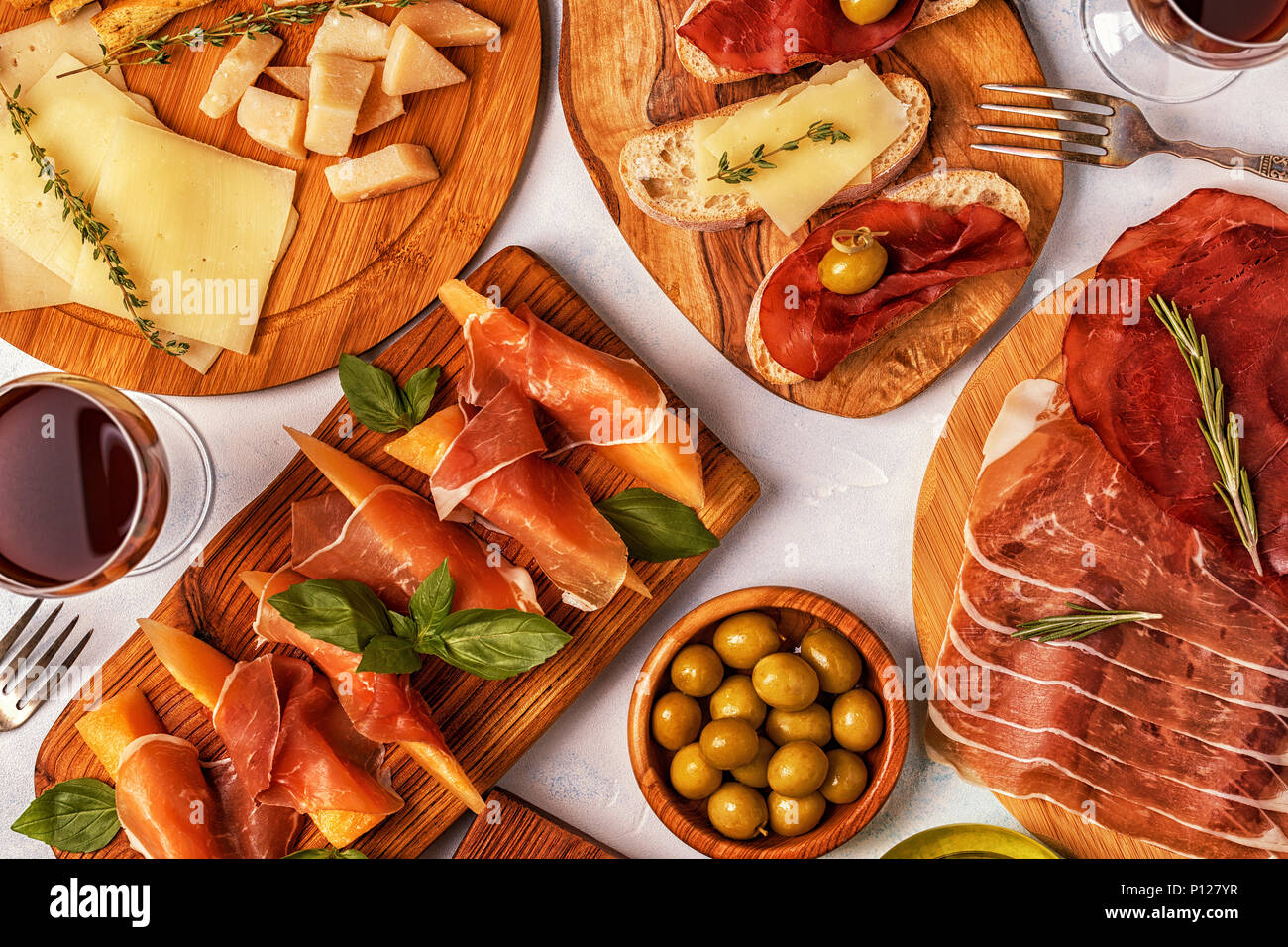 Italian food  background with ham, cheese, olives, bread, wine. - Stock Image