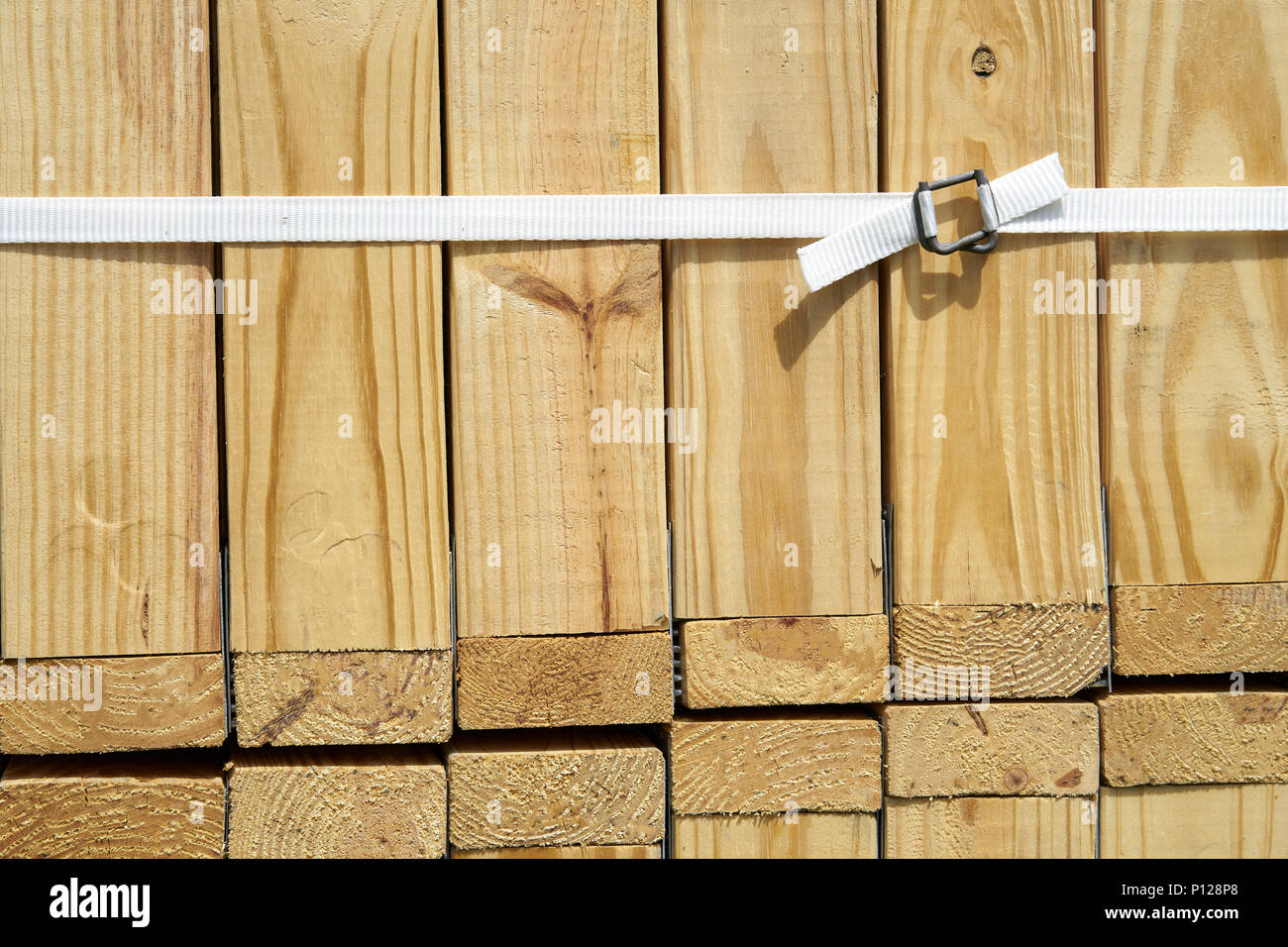 Trusses stack closeup at construction site, white nylon belt with steel buckle , wood background with copy space - Stock Image