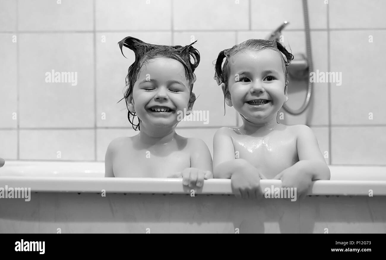 Young children take a bath. Children wash in bathroom. Brother and sister play in the bathroom during water procedures. Stock Photo