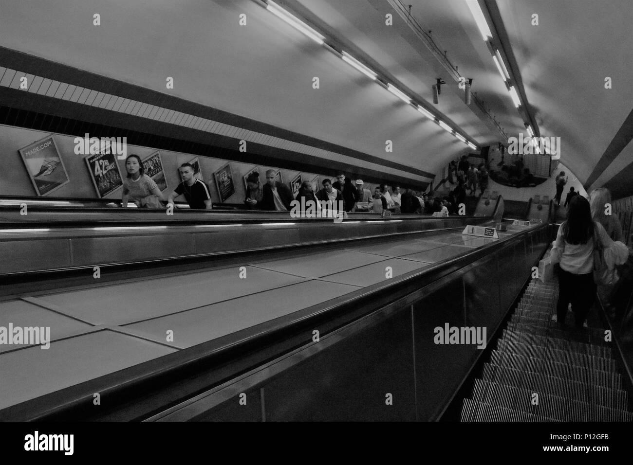 black and White image of people on escalators at London Underground, UK - concept / story image - Stock Image