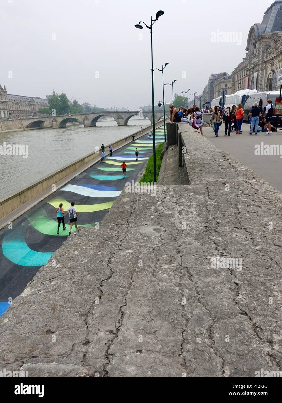 Runners cross an art display painted on the ramp leading down to the Berges de Seine on the  left bank, Paris, France - Stock Image