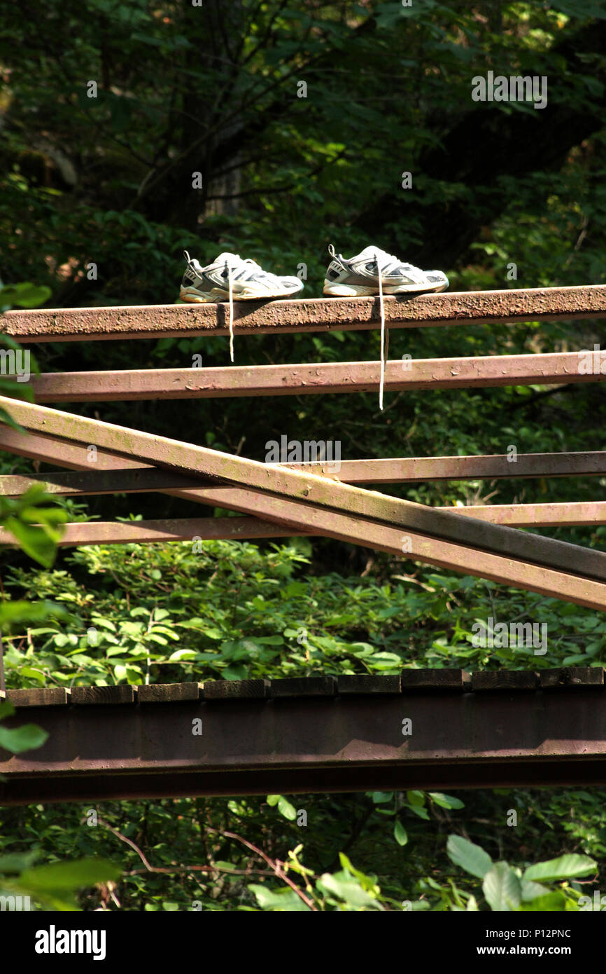 Pair of white snickers drying out in the sun on bridge rail - Stock Image