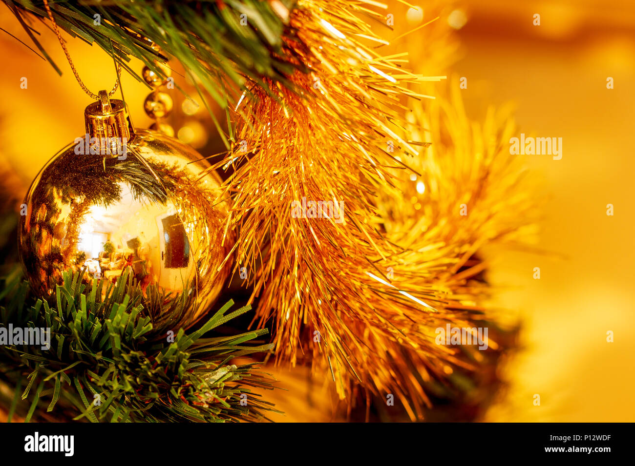 Close up of christmas tree decorations golden color and blur