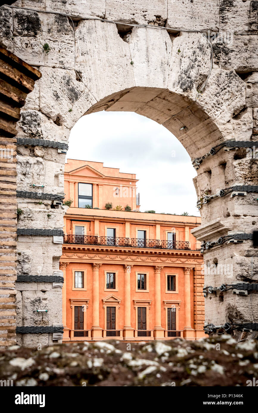 View of modern Roman building through arch in the ancient Colosseum or Colosseo, contrasting old and new, perspective, taken from inside the Colosseum - Stock Image