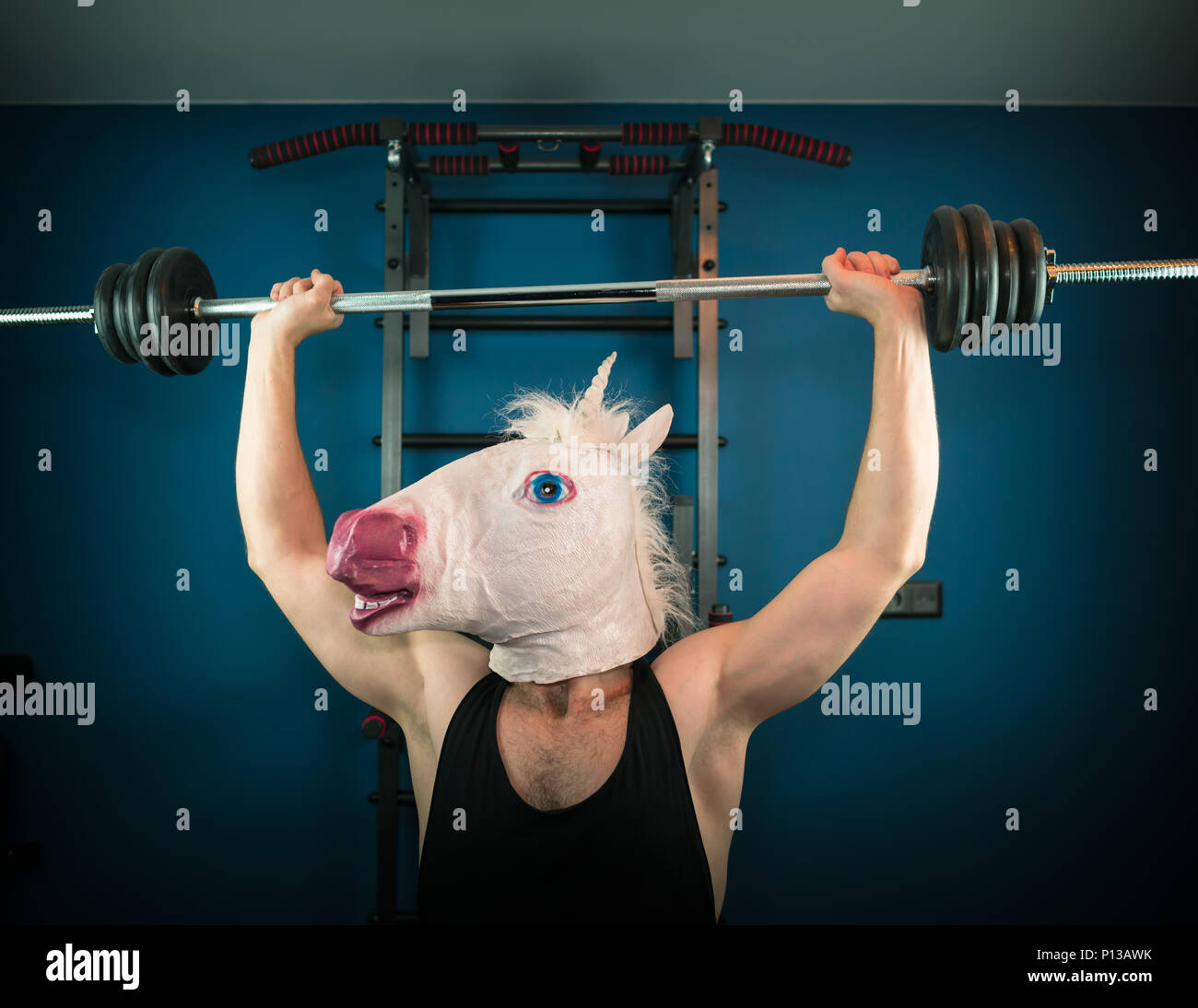 Funny man in comical mask doing sport exercise. Unusual guy pump up iron at home. Unicorn sportsman. - Stock Image