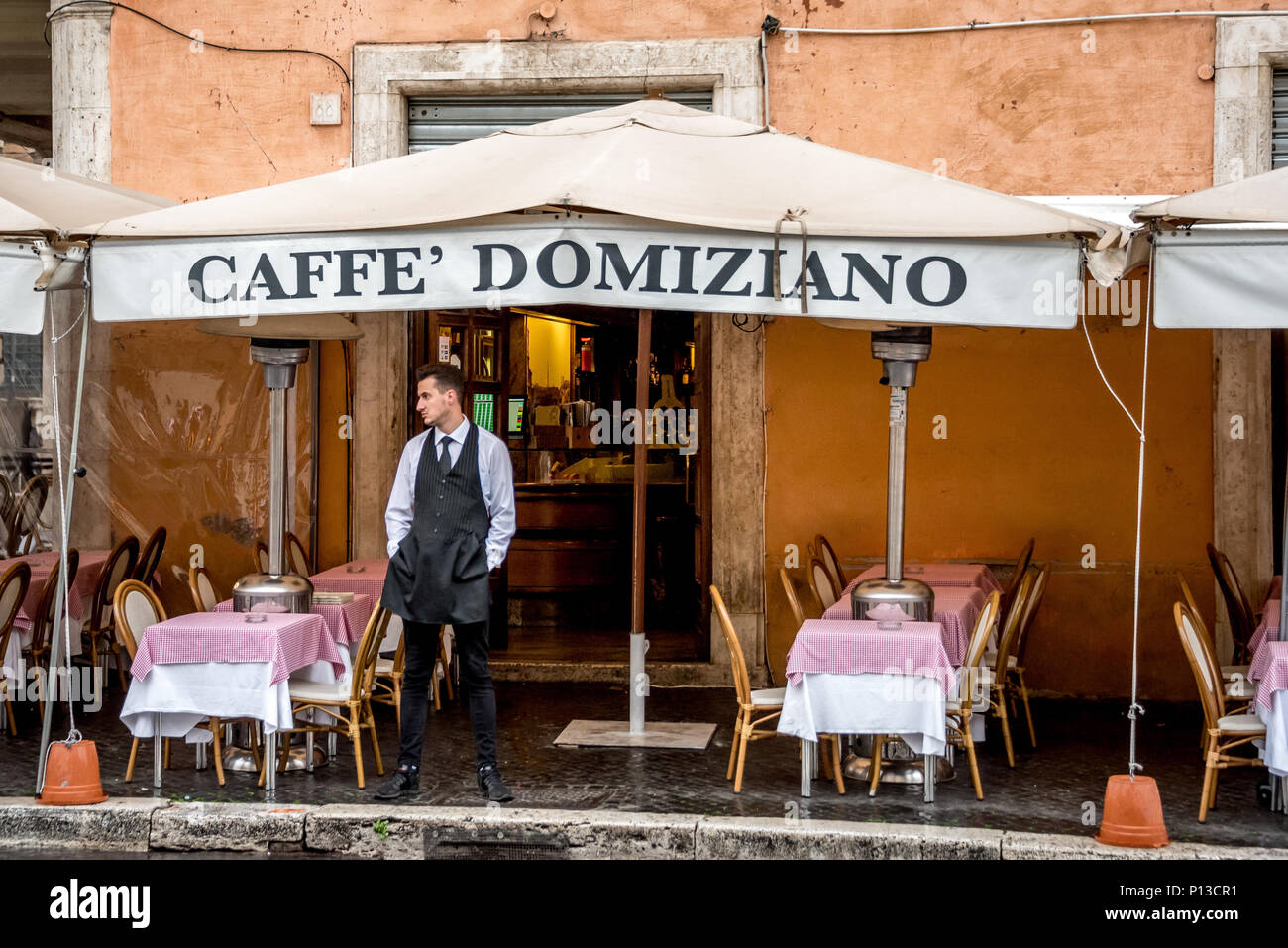 Italian waiter stands outside Caffe Domiziano on Piazza Navona waiting for customers on a rainy day, empty tables, outdoor dining, restaurant name. - Stock Image