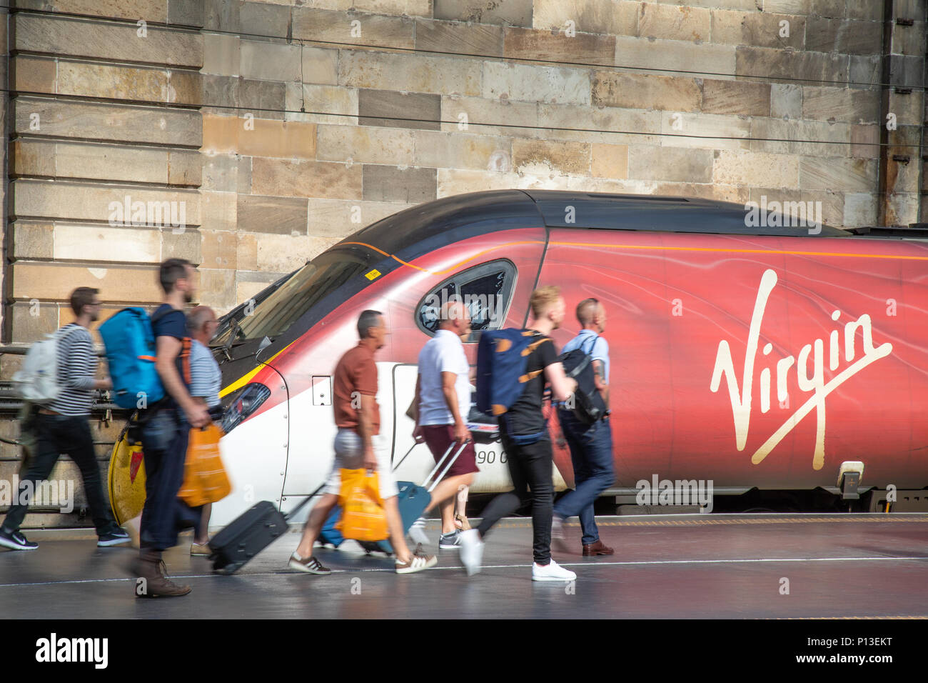 Passengers boarding a Class 390 Virgin Pendolino tilting train at platform one of Glasgow Central - Stock Image