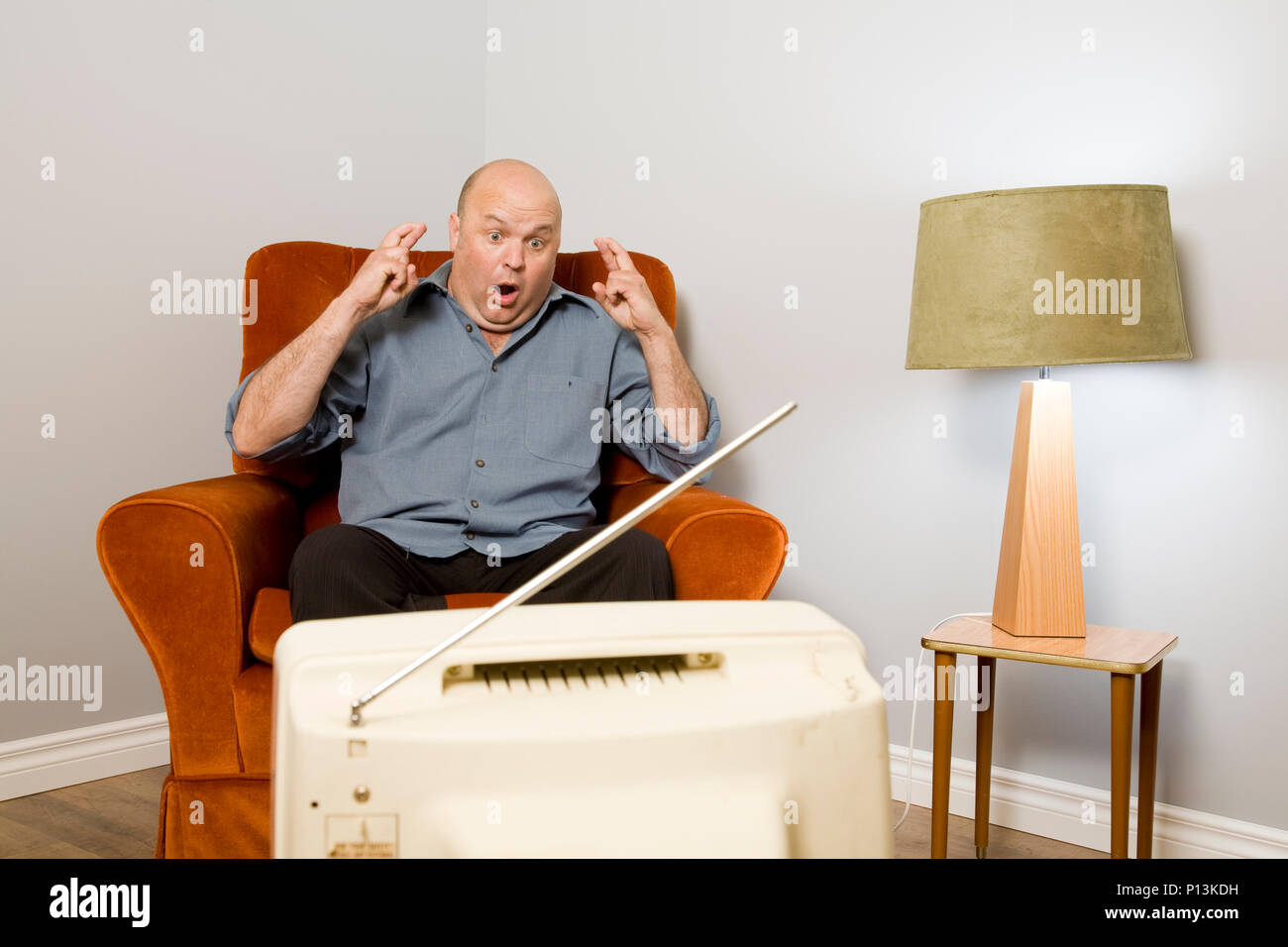 A man with his fingers crossed watching television, perhaps sport or a lottery draw. - Stock Image