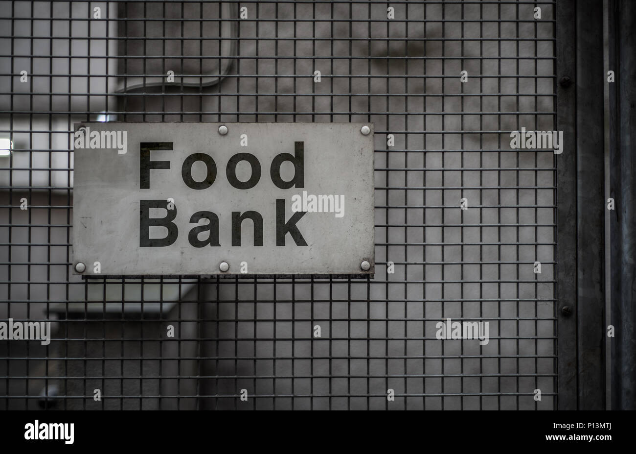 A Grungy Sign For A Food Bank In A Backstreet - Stock Image