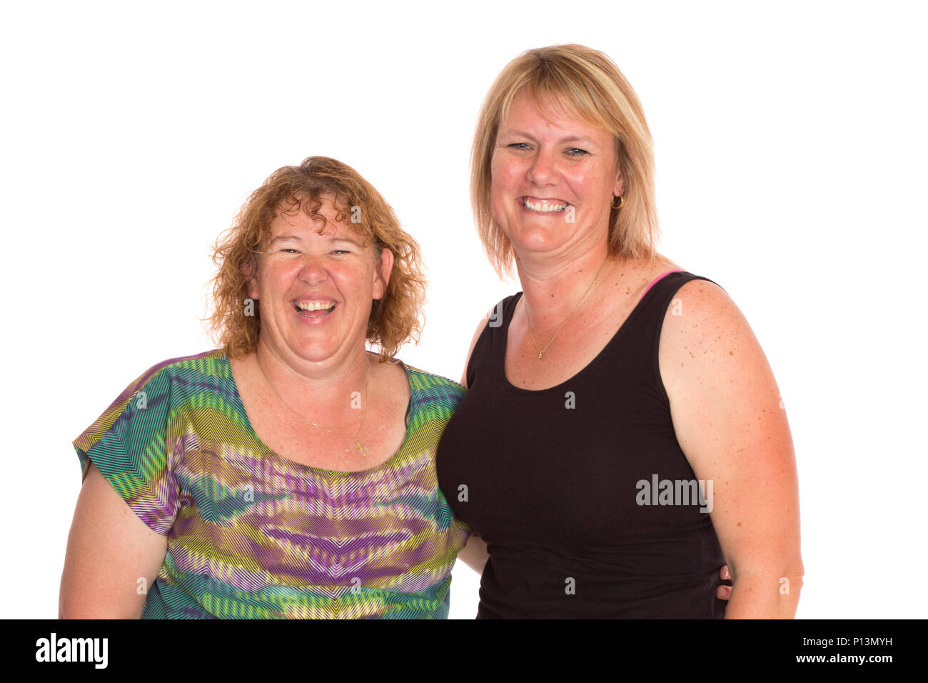 Two average middle aged women standing together for a portrait, on a white background. - Stock Image
