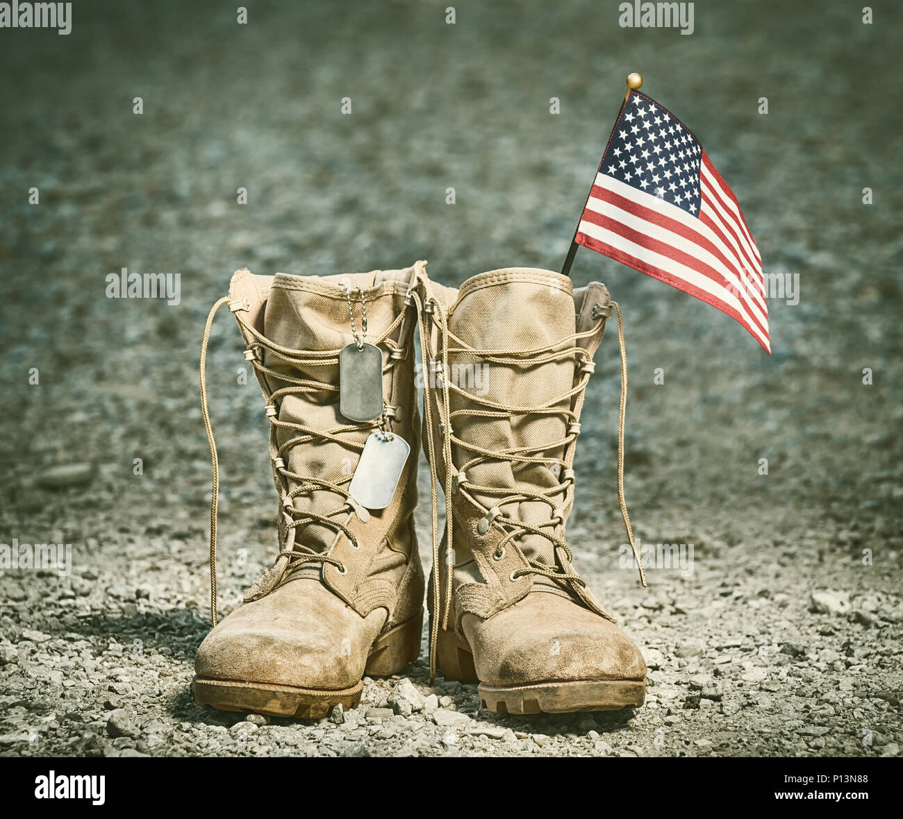 Old Military Combat Boots With The American Flag And Dog Tags Rocky Gravel Background