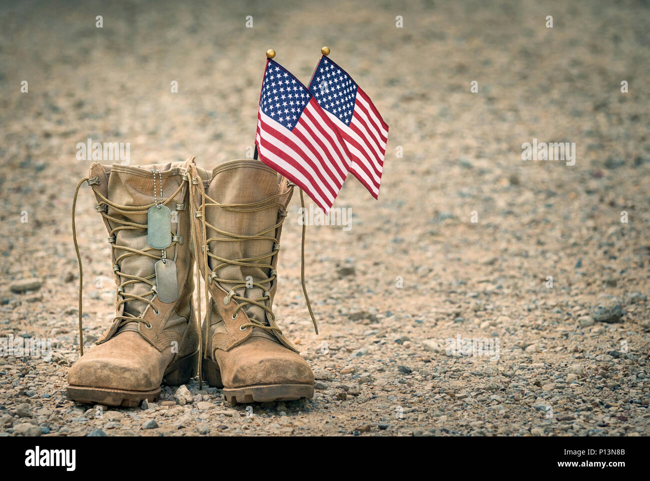 0d70d7cbd1a2 Old military combat boots with dog tags and two small American flags. Rocky  gravel background