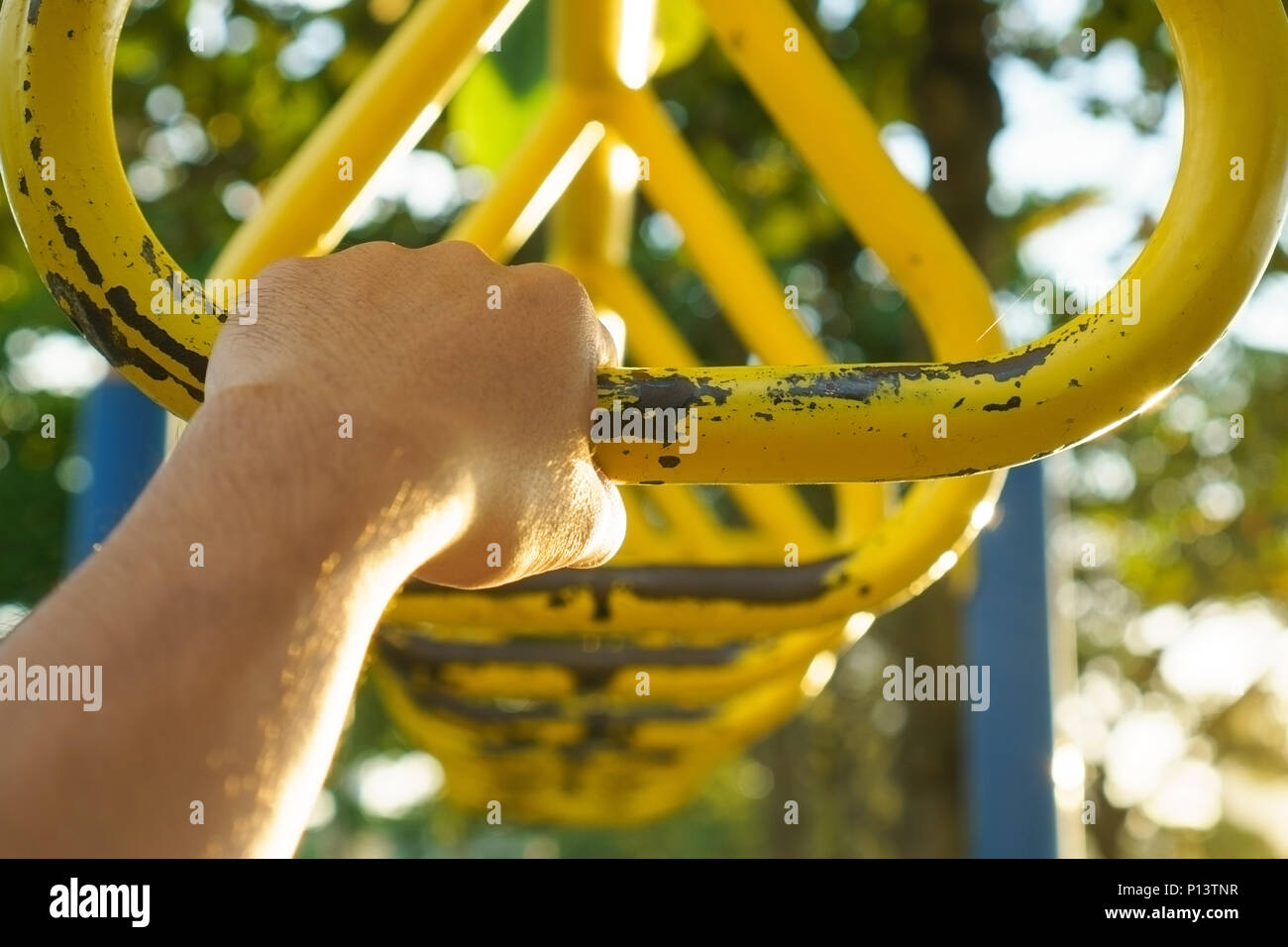 Hand holding metal triangle hanging bar at recreational park. - Stock Image