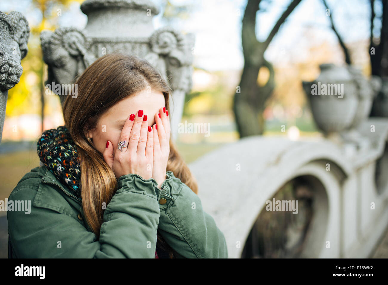 Young attractive woman with red nails covering her face with hands - Stock Image