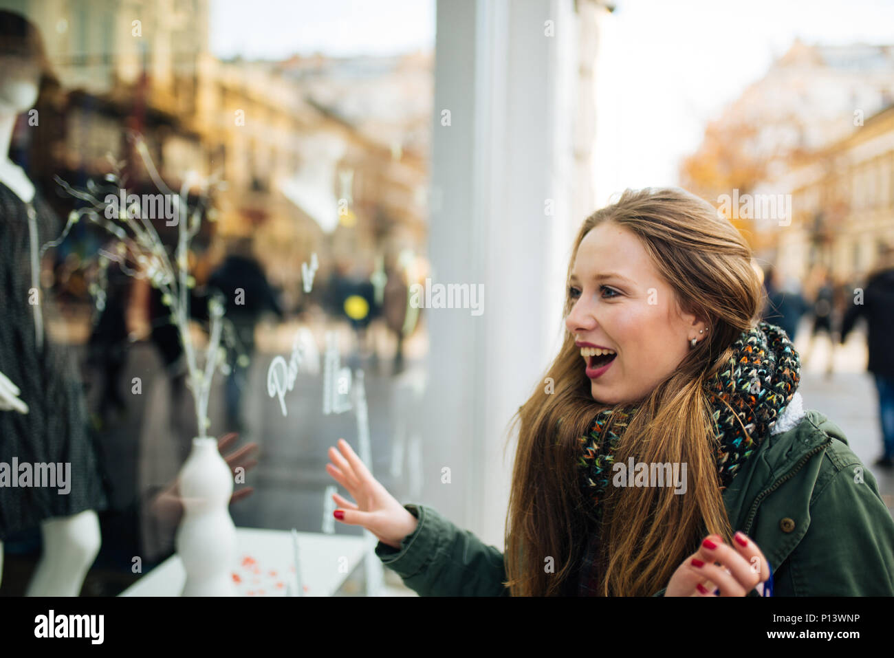 Attractive young long haired woman is excited in front of shopping window - Stock Image
