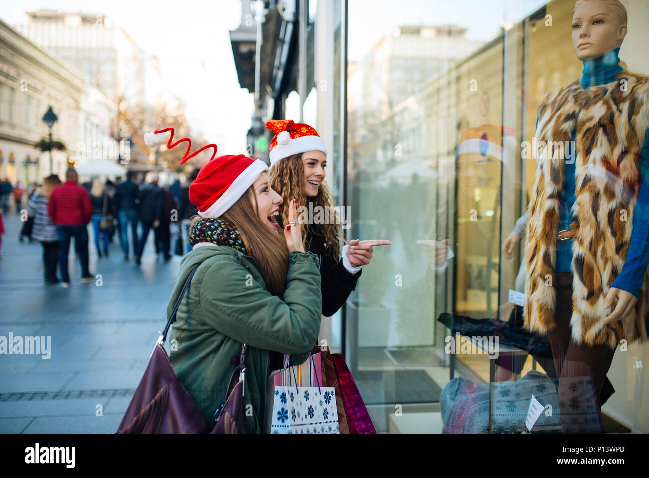 Young attractive woman with santa claus hat in front of shopping window looking to buy something. - Stock Image