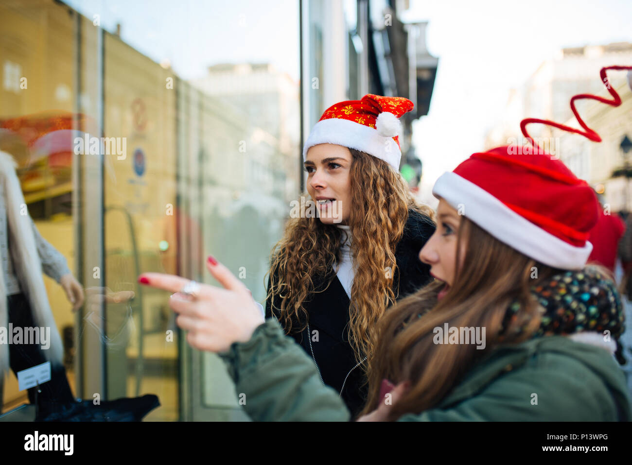 Two attractive young shopaholic with santa claus hats excited looking at shopping window - Stock Image