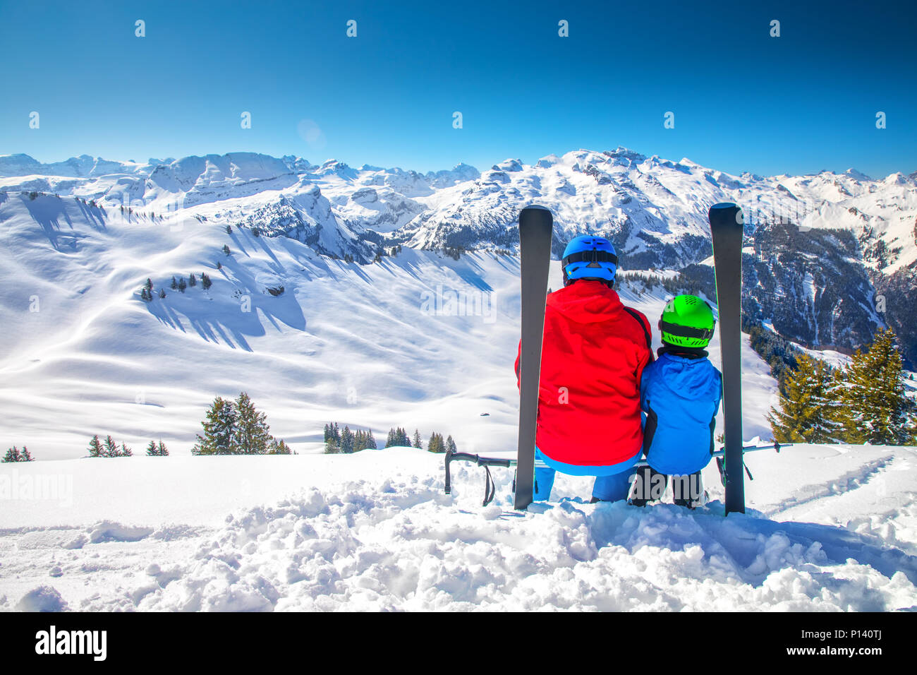 Father with his son skiing and enjoying the view of Swiss Alps, Hoch Ybrig, Switzerland, Europe. - Stock Image