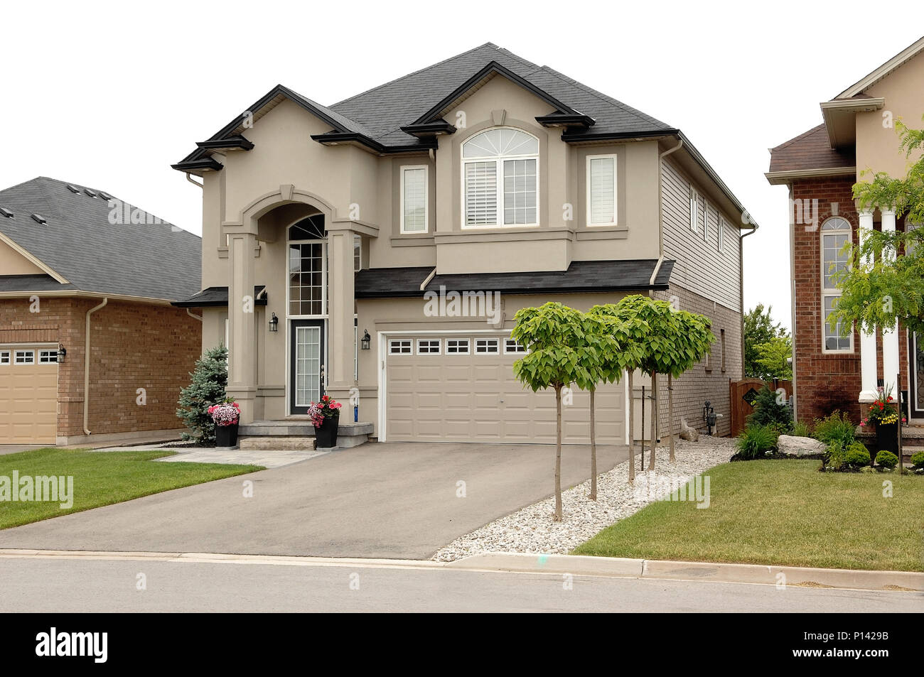 A New Big Two Story House In Subdivision Hamilton Canada With Car Garage And Small Trees