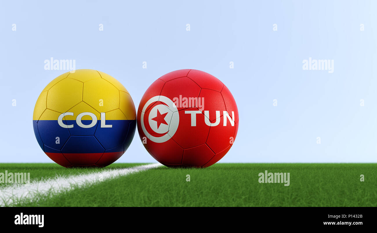 Colombia vs. Tunisia Soccer Match - Soccer balls in Colombia and Tunisia national colors on a soccer field. Copy space on the right side - Stock Image