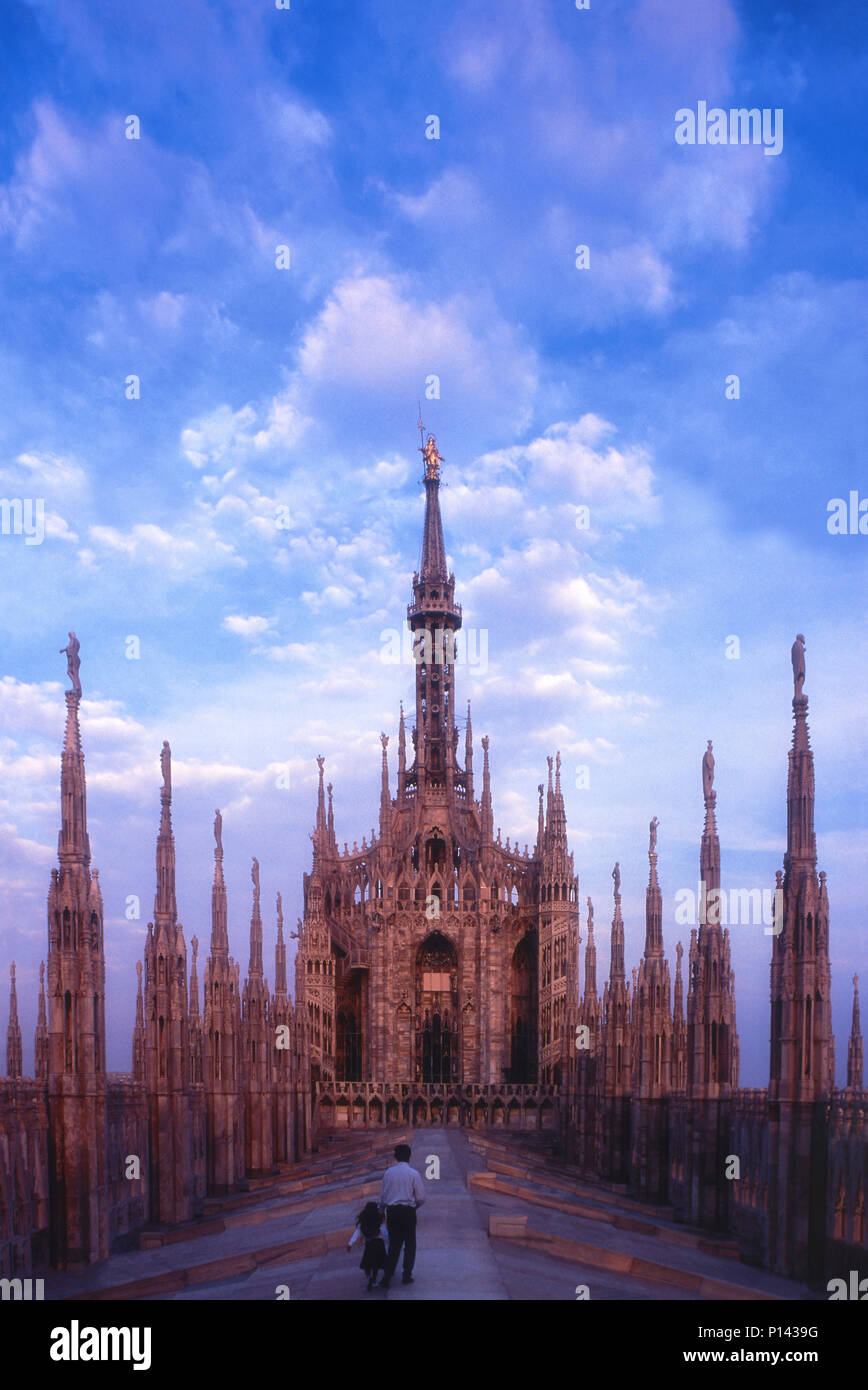 Milan Cathedral, view on roof looking east towards the spire, with father & daughter walking on the roof and moving towards the spire, Milan, Italy Stock Photo