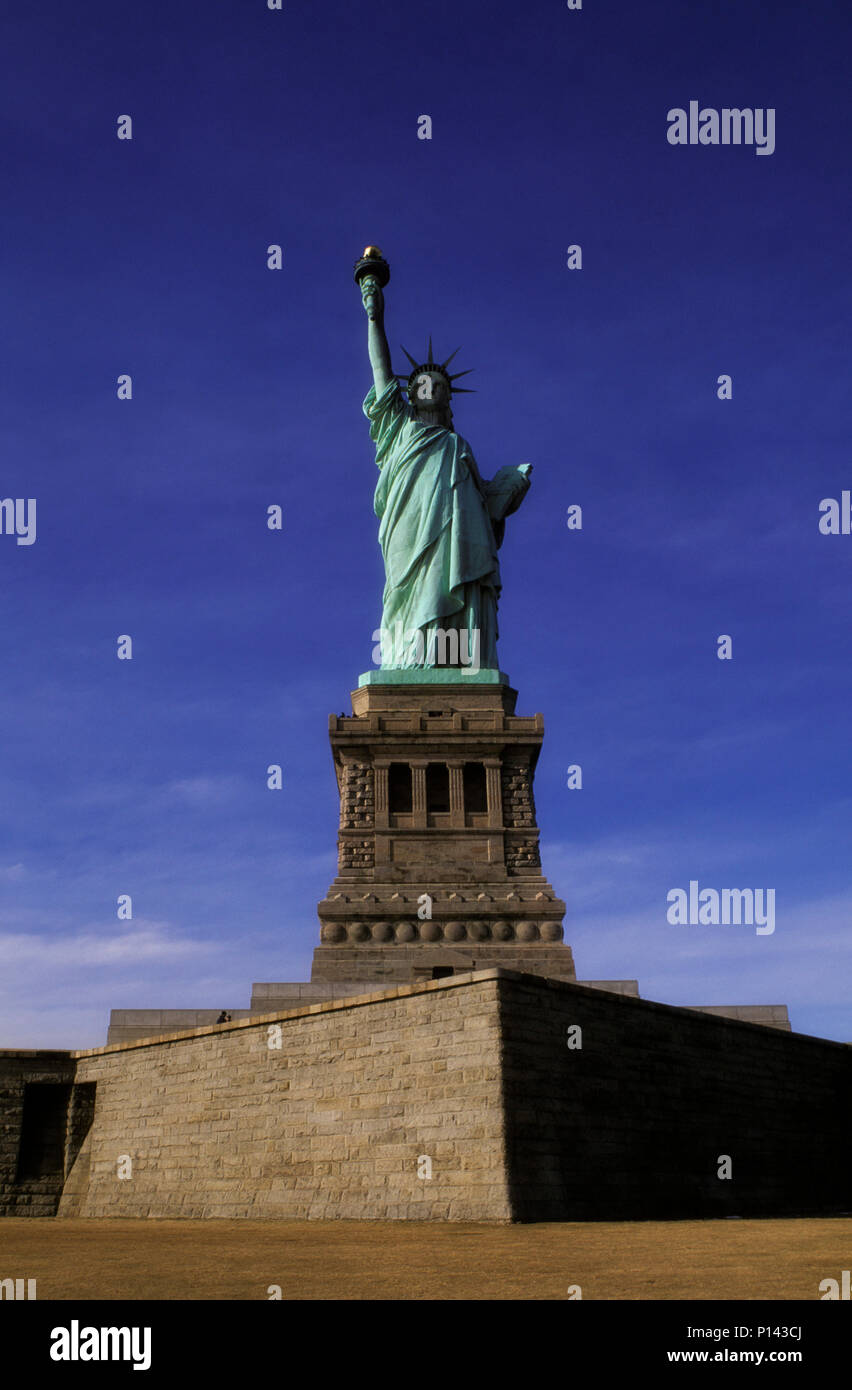 Statue of Liberty, frontal view on axis on Liberty Island with late light and deep shadow, New York, NY, USA - Stock Image
