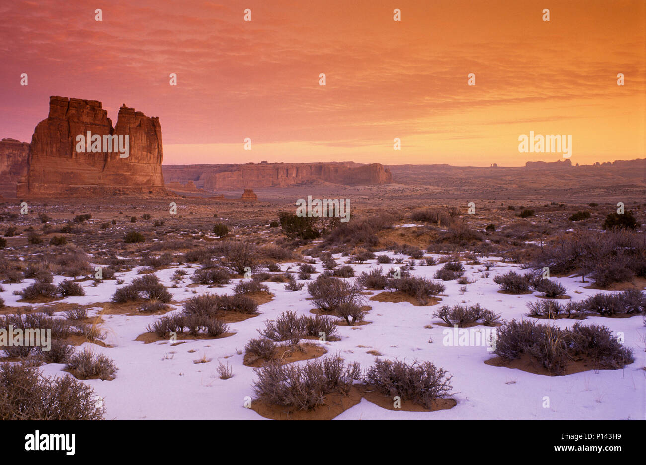 Arches National Park: near Moab, view of canyon and rock formations over snow covered desert at dawn with cloudscape, Utah, USA Stock Photo