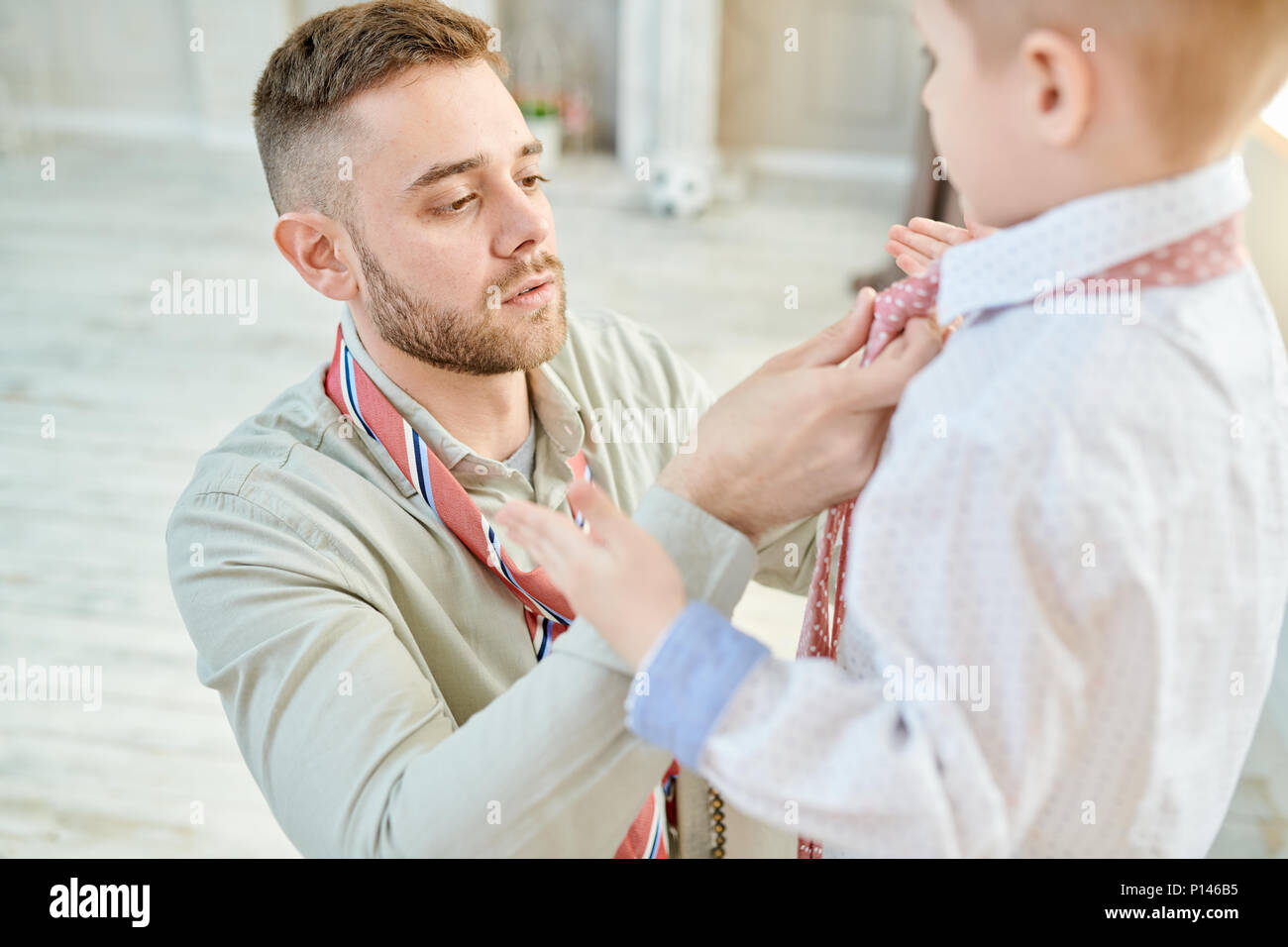 Loving Dad Knotting Tie with Little Son - Stock Image