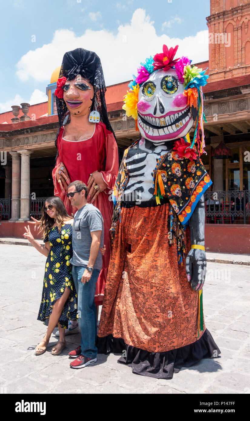Tourist couple being photographed with two giant figures in the center of San Miguel de Allende - Stock Image