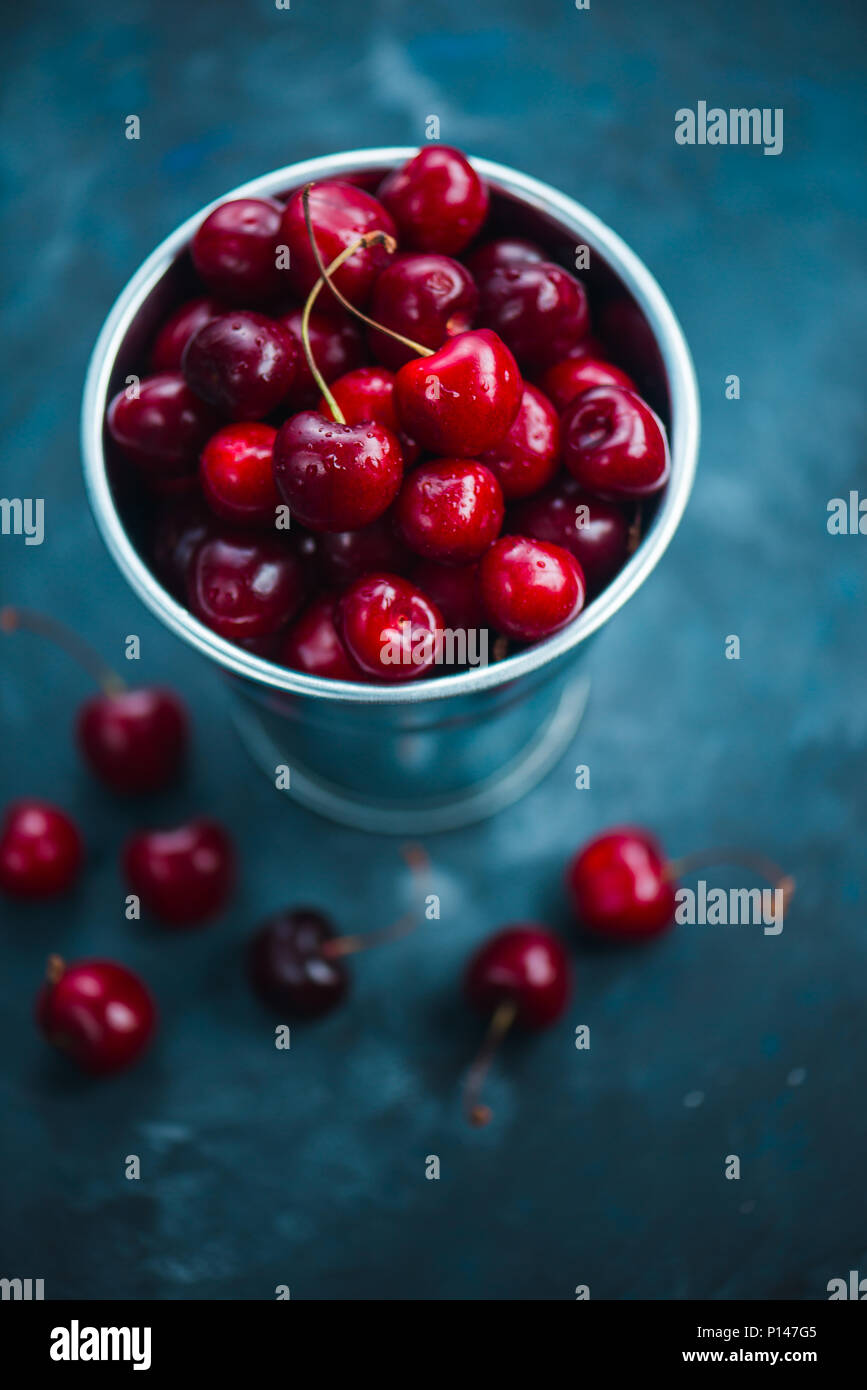Cherries with a small metal bucket on a grey concrete background, summer berries concept with copy space. Neutral color tones still life Stock Photo