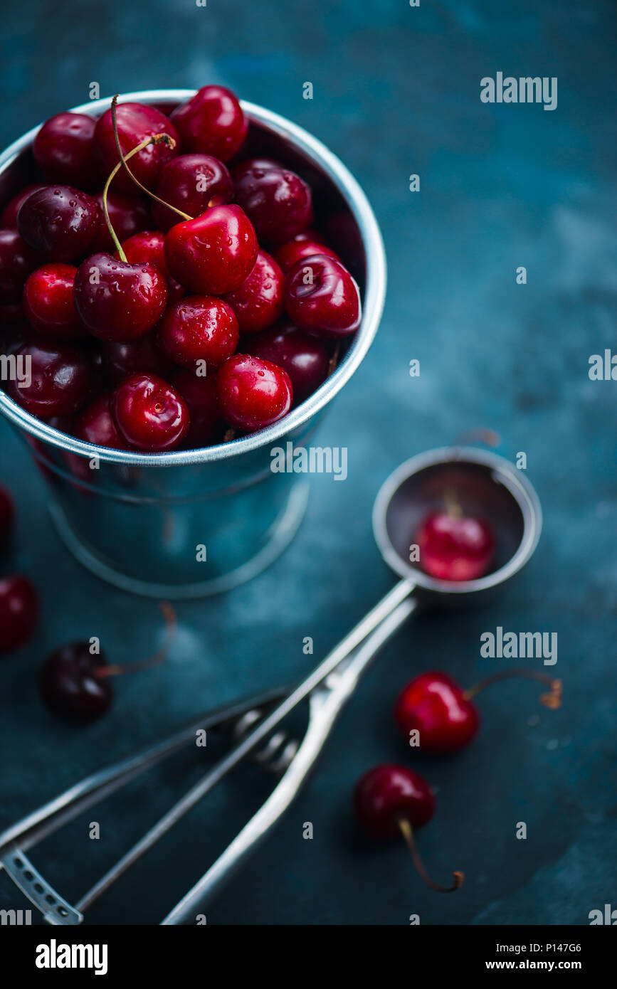 Cherries with an ice cream spoon and metal bucket on a grey concrete background, Summer berries concept with copy space. Neutral color tones still lif - Stock Image