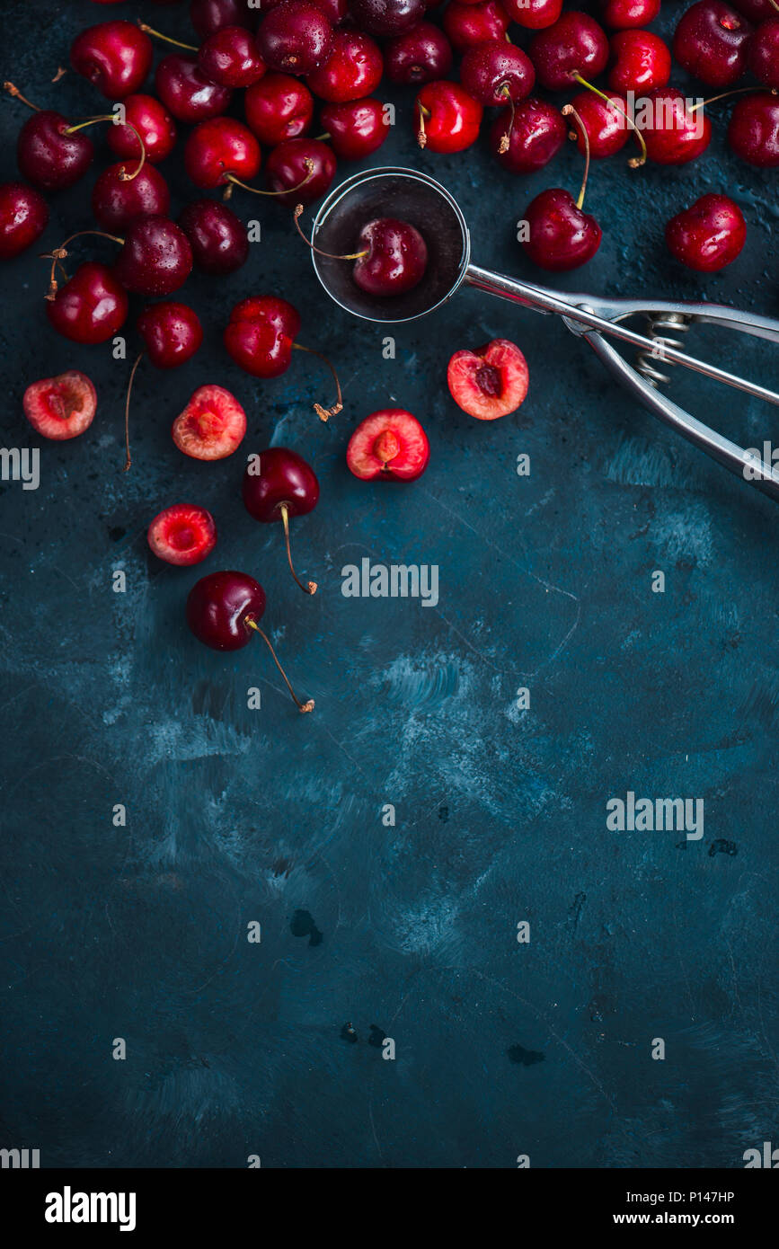 Cherries and ice cream spoon on a grey concrete background, summer berries concept with copy space. Making dessert flat lay in neutral color tones - Stock Image