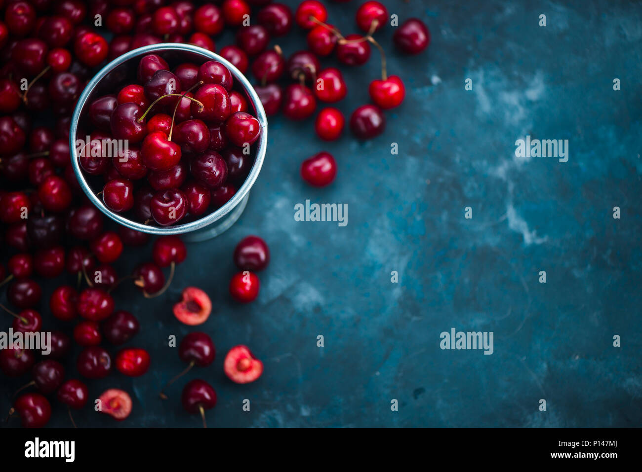 Cherries with a small metal bucket on a grey concrete background, summer berries concept with copy space. Neutral color tones still life - Stock Image