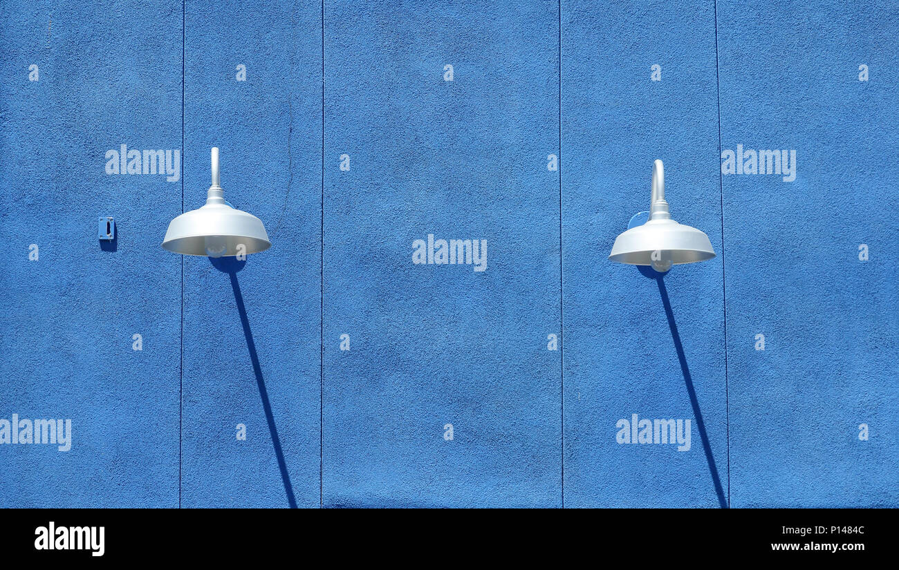 Blue stucco wall with light fixtures and shadows in daytime - Stock Image